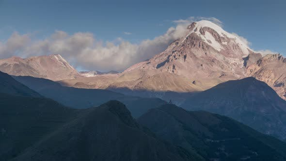 Cover Image for Sunrise in Highlands. Kazbek Mountain Peak with Snow Cap and Glacier in Sun Rays Moving Shadows