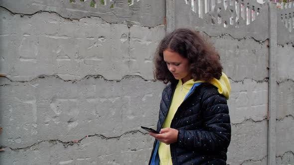 Thumbnail for Teenager Girl Using Mobile Phone on Concrete Fence Background. Young Girl Teenager Browsing