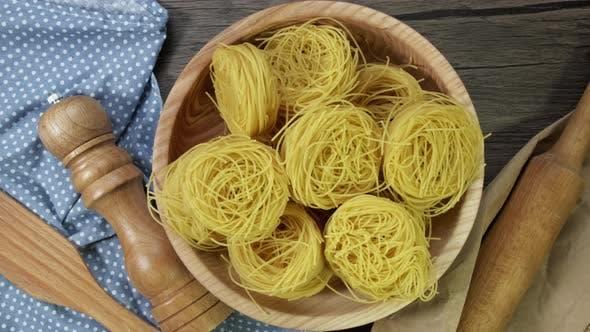 Nahaufnahme von Raw Pasta Drehen an Bord. Fettuccine, Tagliatelle Pasta. Italienische Küche.  Essen