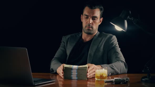 Handsome man plays with a stack of cash