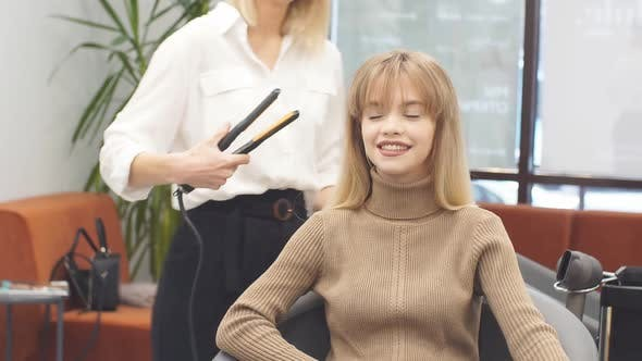Beautiful Caucasian Client Sitting in Hair Salon While Hairdresser Is Combing Her Long Hair