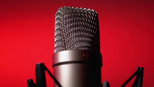 Cover Image for Studio Condenser Microphone Rotates on Red Background.
