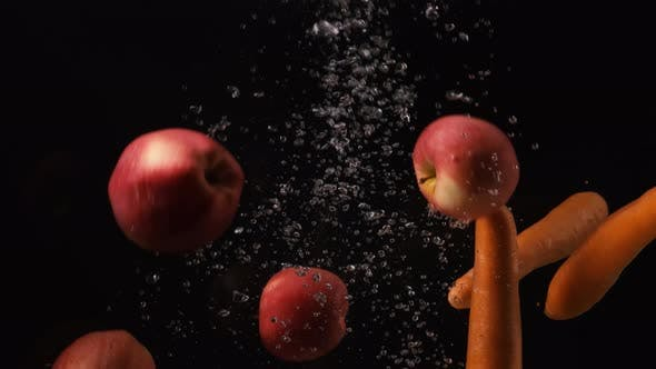 Thumbnail for Carrots and Red Apples Falling Into Water with Bubbles on Black Background. Vegetables and Fruits