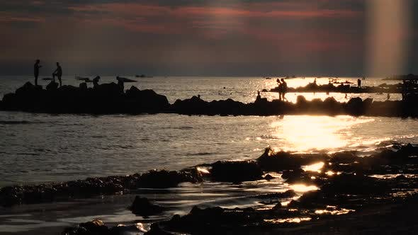 Thumbnail for Sunset People Bathe, in the Sea Beach Swim Boats, Waves Splash About the Shore