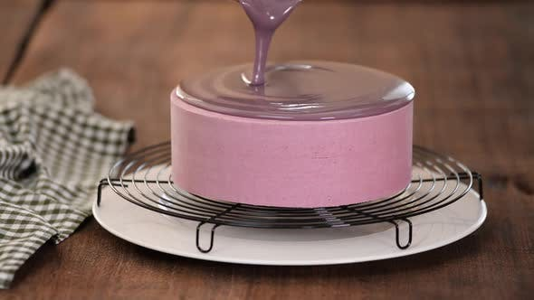 Cover Image for Close up of professional chef covering the glaze cake. Woman decorating cakes with mirrored glaze.
