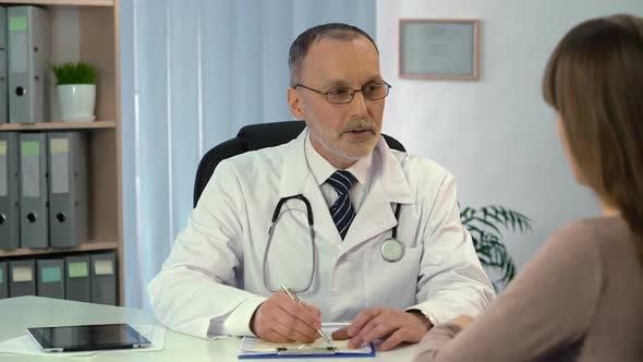 Thumbnail for Aufmerksamer Therapeut in Brillen verschreiben Medizin für Patienten im Krankenhaus