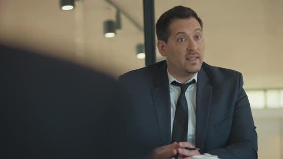 Thumbnail for Mittlere Aufnahme eines Geschäftsmannes, der seinen Kunden eine neue Marketingstrategie präsentiert. Zeitlupe