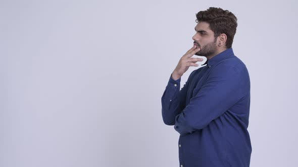 Thumbnail for Profile View of Young Bearded Indian Businessman Thinking