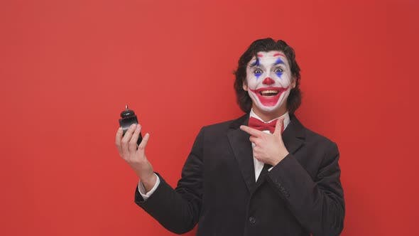 A Clown in a Black Suit with Colorful Makeup on His Face and an Alarm Clock in His Hands Had a Dream