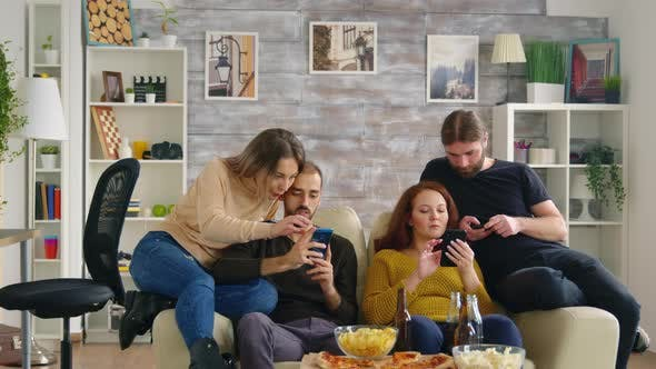 Thumbnail for Group of Friends Sitting on Couch Using Their Smartphones