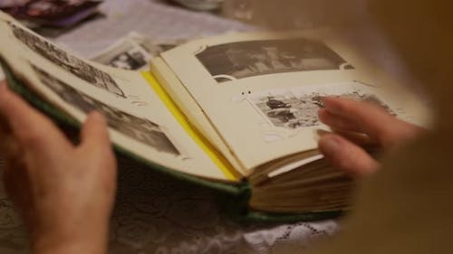 Hand Old Woman Is Looking at Old Photo Album at Home