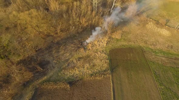 Thumbnail for Aerial View of Farmers Burning Fire on the Field. People Incinerating Dry Leaves and Branches in