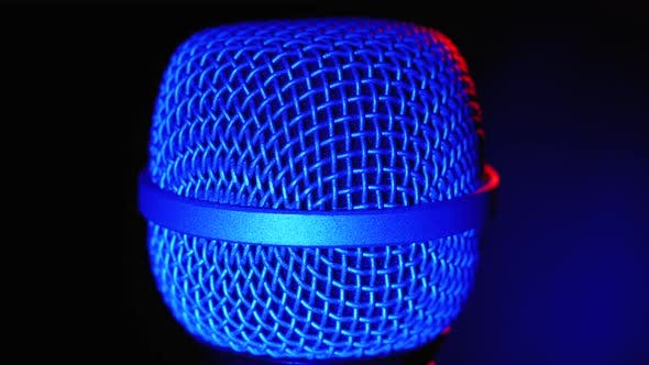 Thumbnail for Microphone Rotates with Blue and Red Backlight. Dynamic Microphone Grid Spins Close-up