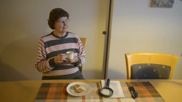 Happy Beautiful Senior Woman Thinking While Drinking Coffee at Home