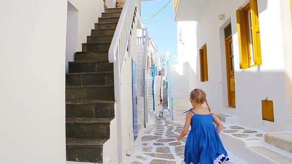 Thumbnail for Two Girls in Blue Dresses Having Fun Outdoors. Kids at Street of Typical Greek Traditional Village