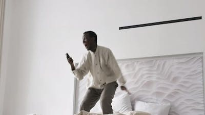 AfroAmerican Man Jumps on Bed Getting Surprised and Happy