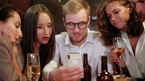 Company of Focused Hipster Friends Using Smart Phone in the Bar, Pub While Caucasian Man Start