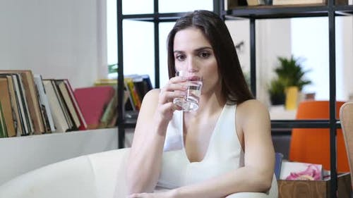 Woman Drinking Water in Glass, Sitting in Office