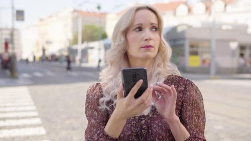A Middleaged Caucasian Woman Works on a Smartphone As She Looks Around Lost in an Urban Area