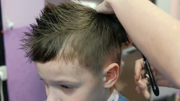 Thumbnail for Barber's Hands Combs and Cutting Blond Short Boy's Hair with Scissors.  Boy's Face.