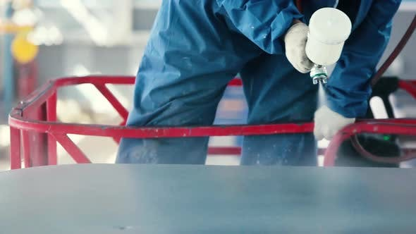Worker Painting steel construction with Spray Pistol wearing mask