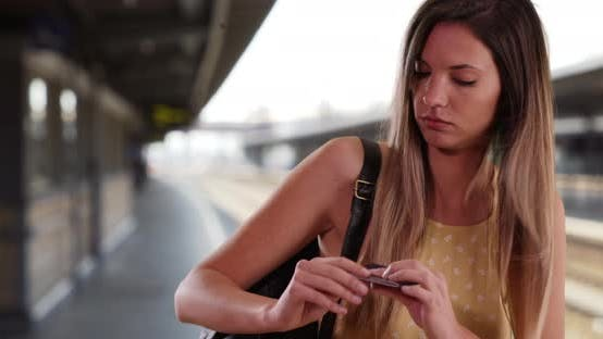 Thumbnail for White American girl taking out passport from backpack waiting for train outdoors