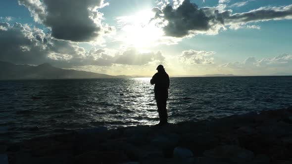 Thumbnail for Man on Edge of Sea Water and Birds Feed