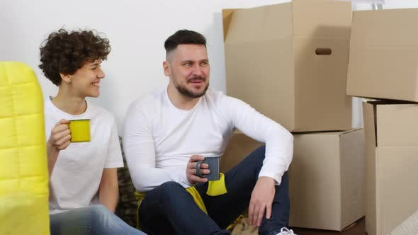 30-something Caucasian Couple Chatting in New Apartment