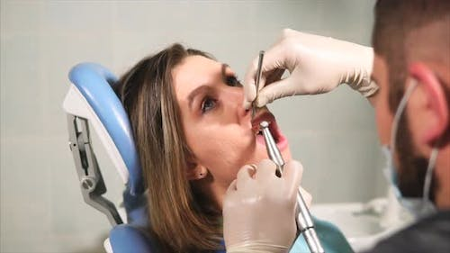 Doctor Dentist Cleans Teeth for Young Woman From Plaque and Tartar