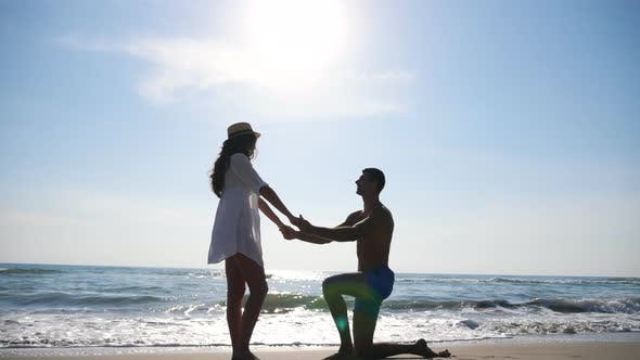 Cover Image for View on Newlyweds at Seascape Background. Young Man Stand on Knee and Marriage Proposal To His