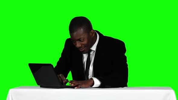 Cover Image for Businessman Sitting at a Desk and Using Laptop. Office Work. Green Screen