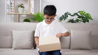 Boy wearing glasses opening gift box