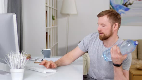 Thumbnail for Man Doing Bicep Curl with Water Bottle and Typing on Computer