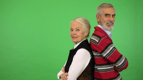 Thumbnail for An Elderly Couple Stands with Their Backs To Each Other and Smiles at the Camera