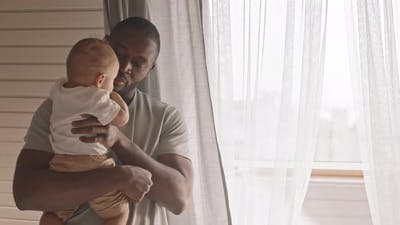 Father Holding Child at Home