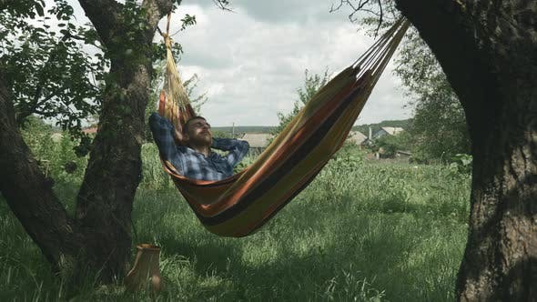 Happy young man relaxing on hammock in garden. Tourist relaxing in hammock. Male lying in hammock