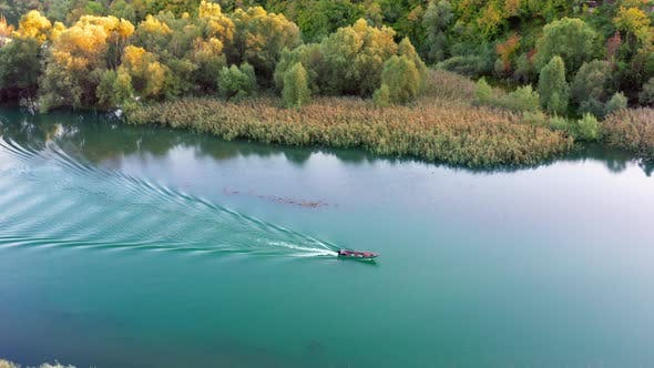 Thumbnail for Small boat is sailing on the calm lake in autumn, leaving rippled trail behind