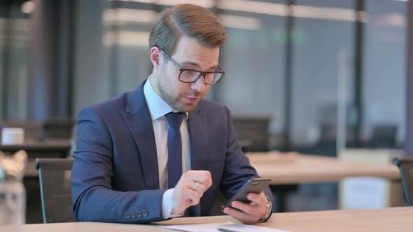 Businessman Celebrating Success on Smartphone