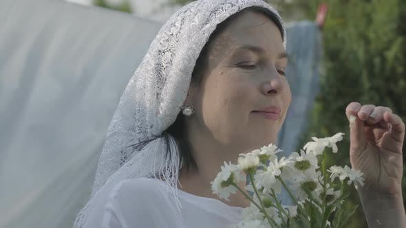 Thumbnail for Senior Woman with White Shawl on Her Head Sniffing Daisies Near the Clothesline Outdoors
