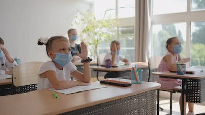 Children in the Classroom at School in Masks Sit in the Classroom and Answer the Teacher's Questions