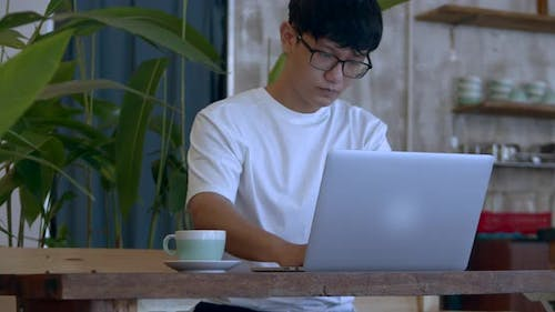 Man Asian in Glasses a Teenager, Working on a Laptop Looks at the Screen While Sitting in a Cafe