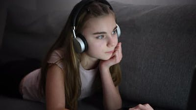 Girl with Headphones Enjoying Online Learning in Front of Her Laptop Computer
