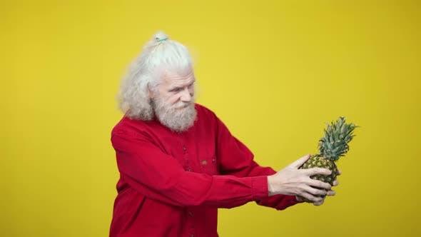 Thumbnail for Joyful Senior Man Dancing with Pineapple at Yellow Background