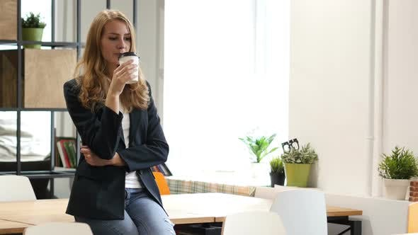 Thumbnail for Drinking Coffee Businesswoman, Sitting on Desk