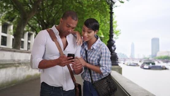 Liebevolles ethnisches Paar mit Smartphone zusammen außerhalb in London