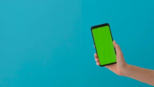 Female Hand Holding Smartphone with Green Screen