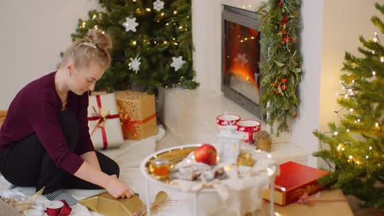 Woman Wrapping Christmas Present By Fireplace At Home