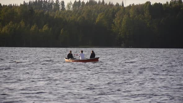 Thumbnail for Young adults racing and rowing a boat on a lake at sunset.
