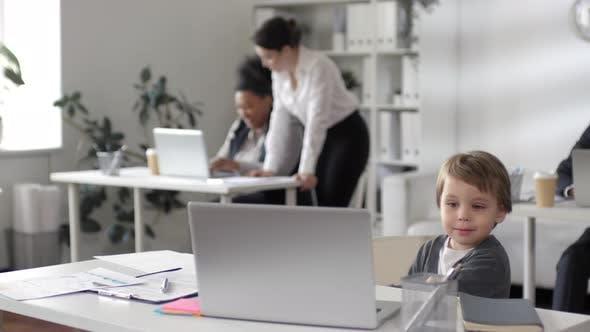 Thumbnail for Kleines Kind sitzt am Schreibtisch während Mutter arbeiten