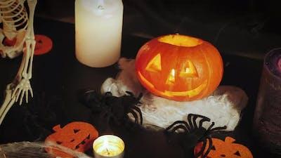 Lighting carved orange pumpkin in dark room.